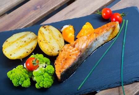 Delicious roasted salmon and potatoes served with fried egg yolk, fresh vegetables and greens on black plate