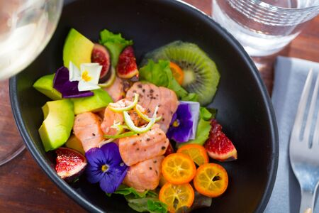 Freshly prepared salmon ceviche with avocado, lime, figs, kumquat and edible flowers