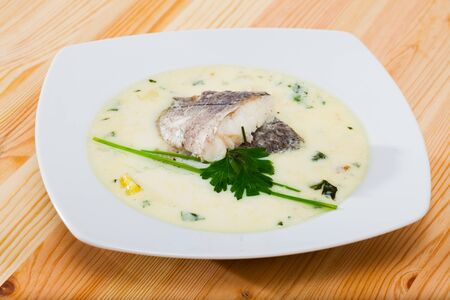 Delicious soup with smoked haddock, potatoes and onions served with greens in white bowl - traditional dish of Scottish cuisine Фото со стока - 129816704