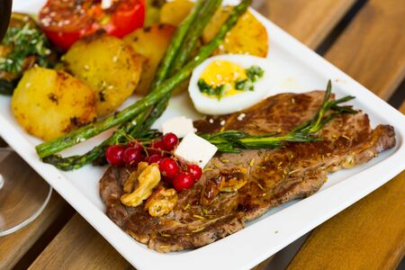 Veal with baked vegetables is tasty dish in the kitchen. Фото со стока - 129816711