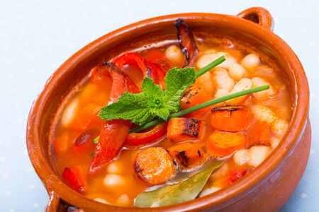 Bulgarian cuisine. Bob chorba - delicious spicy bean pottage with pepper, carrots and tomatoes in clay soup bowl