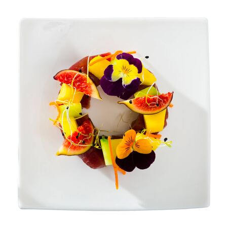 Top view of raw tuna tartare served with white wine glass on plate with figs and cucumber garnished with pansies flowers. Isolated over white background