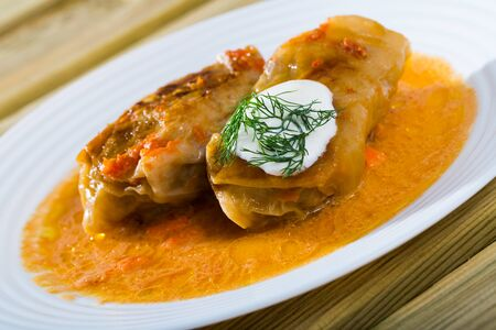 Cabbage rolls in cabbage leaves with sour cream,  dish of Eastern European cuisine