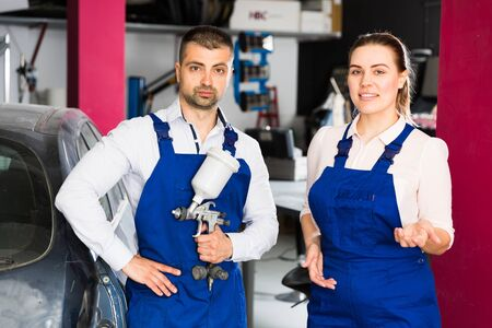 Two professional mechanics welcoming in modern car painting workshop Stock Photo
