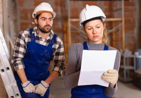 Female foreman checking the work of the builders in house Stock Photo - 129816282