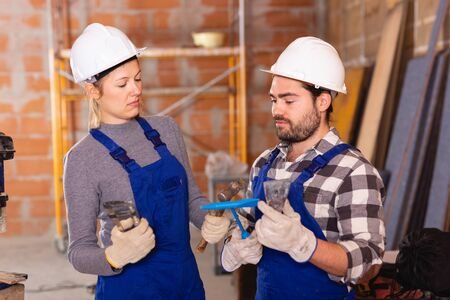 Portrait of two confident workers in uniform with tools inside brick cottage