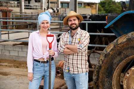Confident young man and woman owners of dairy farm standing near tractor outdoors