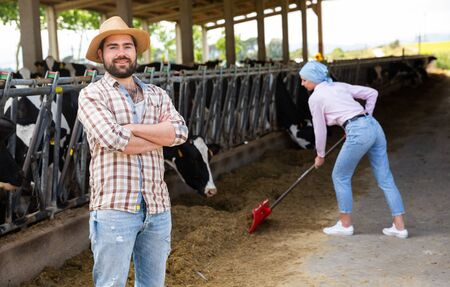 Confident young man owner of dairy farm standing in stall on background with herd of cows