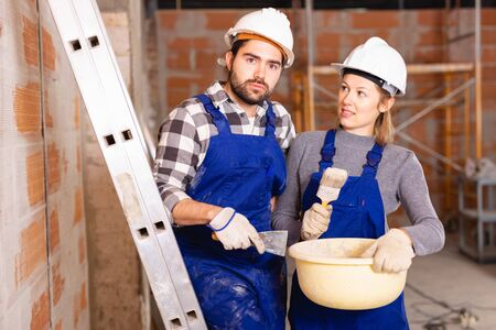 Portrait of two painters inside a cottage under construction Stock Photo - 129816431