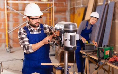 Man is worker behind drilling machine