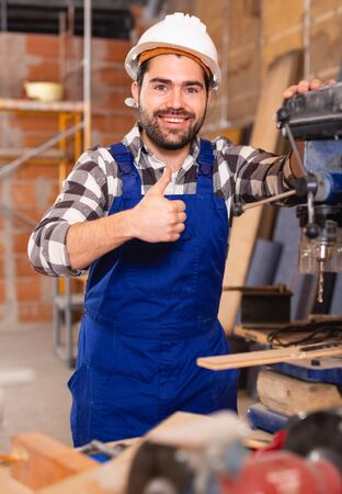 Positive worker behind the drilling machine