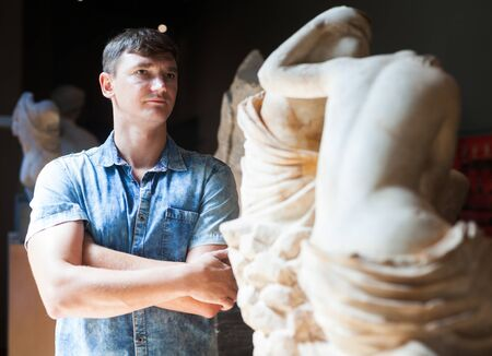 Young man visiting Museum of History and looking at ancient sculptures Banco de Imagens