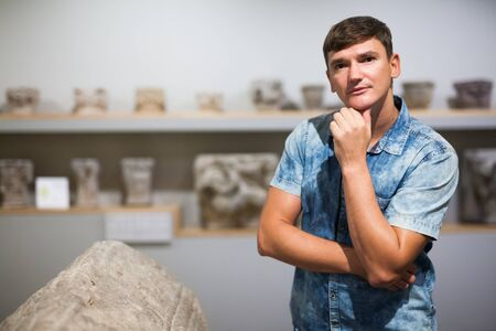 Young man looking at stone architectural elements of Ancient Greece in historical museum