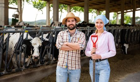 Portrait of confident successful farm family engaged in breeding of cows posing in cowshed