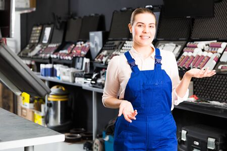 Positive girl in workwear standing near stand with paints in car repair shop, meeting clients Stock Photo