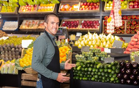 Portrait of friendly male shop assistant standing in front of the counter of vegetable shop Фото со стока