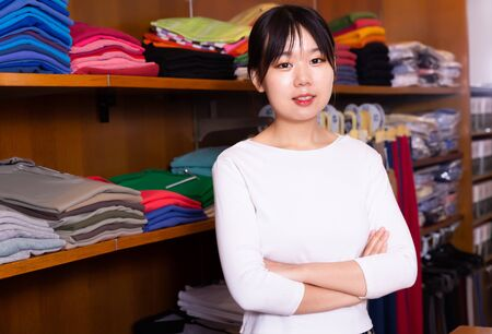 Chinese female shopping assistant offering various shirt in men's cloths store