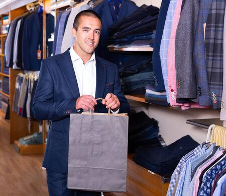 Happy man holding paper bag after shopping in modern clothing store