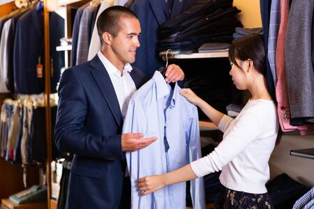 Female shopping assistant offering various shirts in mens cloths store