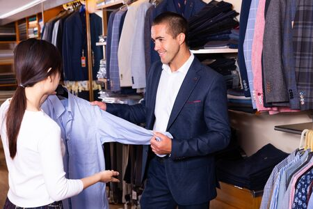 Portrait of young family couple looking for new dress shirt in men clothes shop