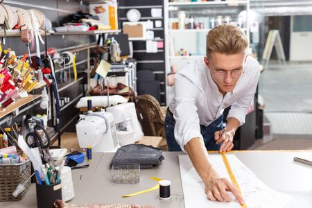 Professional male dressmaker at work – creating pattern at his workplace Stock Photo
