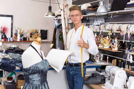 Portrait of cheerful young male fashion designer at sewing atelier