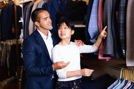 Portrait of young positive smiling family couple looking for new suit jacket in men clothes shop