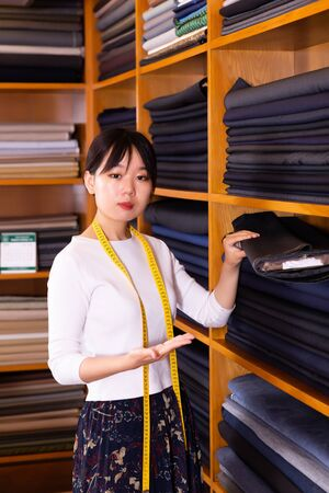 Competent young saleswoman offering various interesting cloth in textile shop