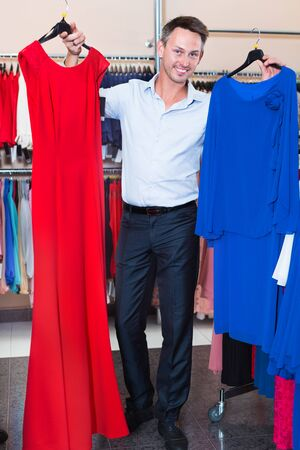 Young smiling man helping girlfriend to choose gown at a clothes store Stockfoto