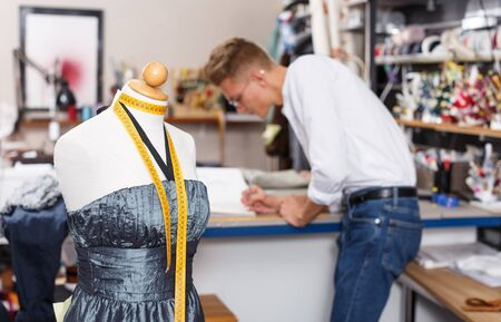Close up view of tailor mannequin and male tailor at work on background