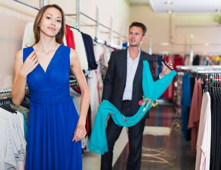 man helps a woman decide on an elegant dress in a clothing store