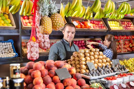 Young man selling fresh kiwi and other fruits at supermarket