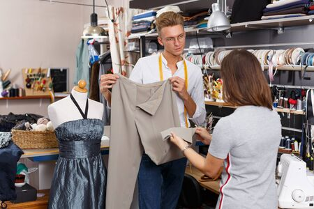 Professional male tailor showing customer trousers at sewing atelier 写真素材