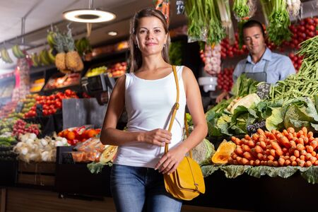 Cheerful female customer standing near counter with fresh fruits on the supermarket