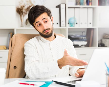 Elegant young businessman sitting at office desk and working at laptop Banco de Imagens