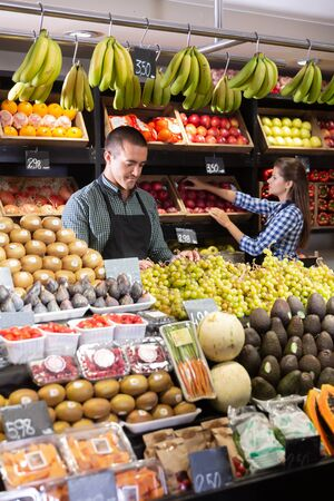 Posing adult male  and working woman in fruit and vegetable shop