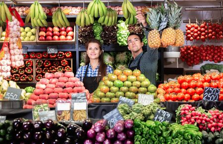 Friendly diligent positive cheerful smiling man and woman laying out vegetables and fruits in shop