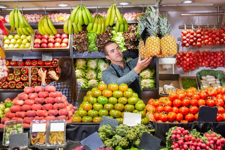 Portrait of male and female shop assistants working in the fruit and vegetable shop