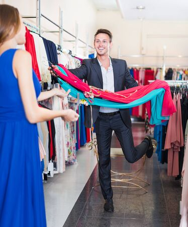 Young smiling man helping girlfriend to choose the gown at clothes store