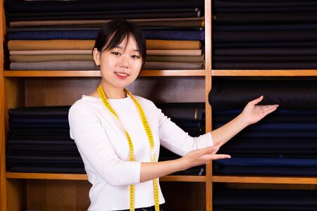 Portrait of chinese girl tailor in a mens clothing store Stock Photo