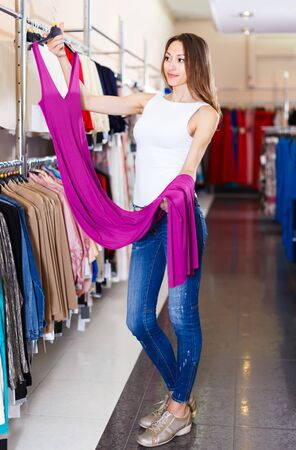 positive brunette female selecting new dress in fashionable showroom Stockfoto