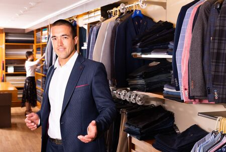 Positive male customer choosing fashion suit in mens store Stockfoto