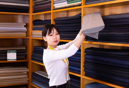 Professional seller of fabrics in clothing store