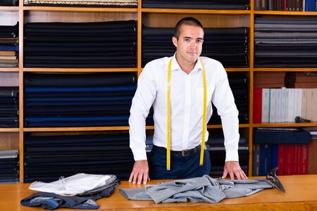 Confident salesman standing next to cutting table in textiles store