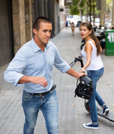 Angry young male  bandit is stole the handbag from stranger female on the street