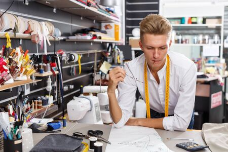 Professional male dressmaker at work – creating pattern at his workplace