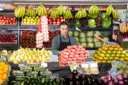 Young man seller in an apron, in the department with fresh vegetables in the supermarket, a woman in the background