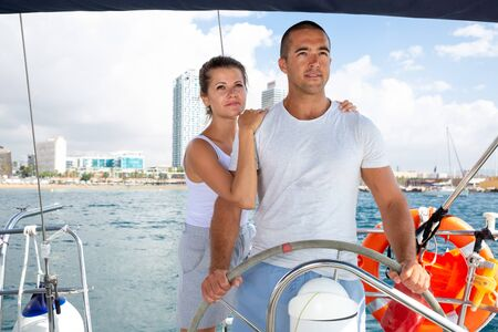 Cheerful couple steering yacht in calm blue sea along Spanish coast during romantic summer vacation Stok Fotoğraf