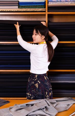 Portrait of positive Chinese salesgirl working in fabric store, demonstrating wide range of stylish cloth