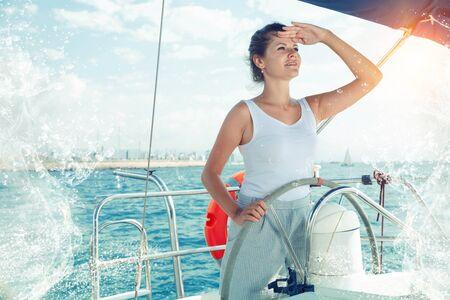 Lächelnde selbstbewusste Frau, die an einem sonnigen Sommertag auf ruhigem blauem Meer eine Vergnügungsyacht steuert?